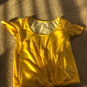 A relaxed yellow button up T-shirt
